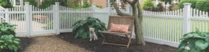 A puppy sits next to a pet safe fence